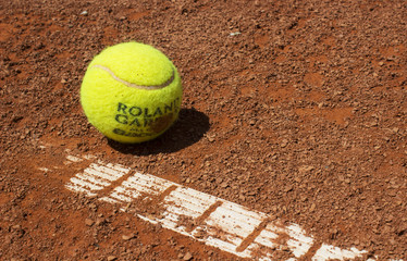 tennis ball on red clay