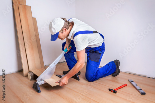 Male Worker laminate flooring.