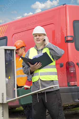 Electricians with cell phone and folder near switchboard
