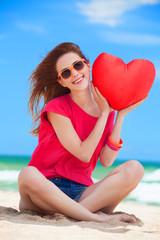 Redhead teen girl with heart shape on the beach