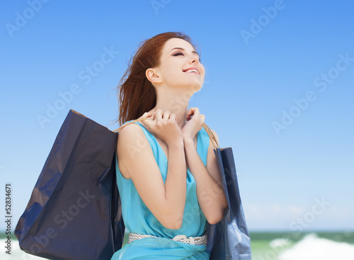 Redhead teen girl with shopping bags on the beach