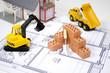 Miniziegelsteine auf Bauplan mit Baufahrzeugen