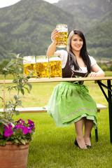 junge frau im dirndl am biertisch prostet mit maß bier