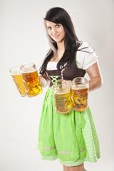 junge Frau im Dirndl mit vier Maß Bier in der Hand