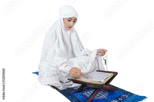 Beautiful female muslim read Kuran - isolated