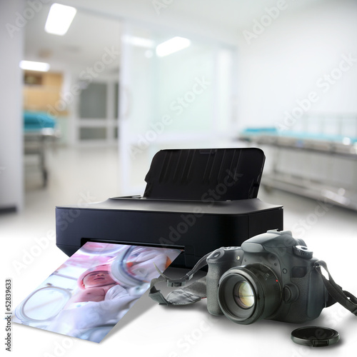 Camera and printer with picture of a newborn baby in the hospita