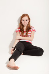 portrait of cute redheaded girl, background white wall