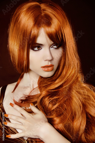Healthy Long Hair. Beautiful woman with red curly hair and eveni