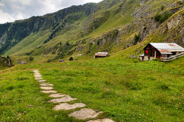 hiking path with wooden huts, Switzerland