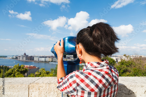 Woman seeing the city over a river through binocular