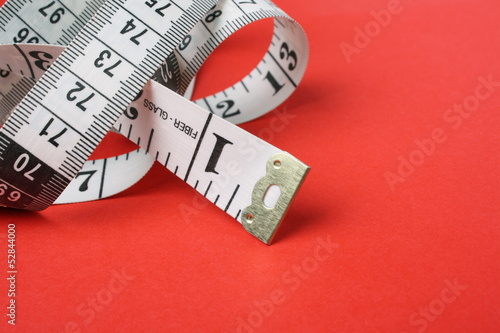 White Tape Measure on Red Background