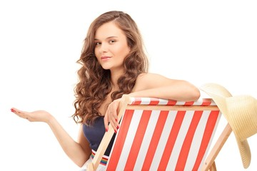 Young woman sitting on a sun lounger and gesturing with hand