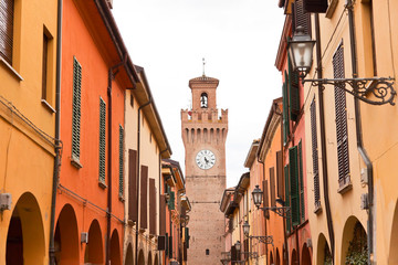Street with houses and tower with clock in Castel San Pietro. Em