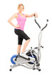 Young woman posing on a cross trainer fitness machine