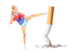 Female with boxing gloves kicking with her leg a cigarrette butt