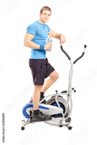 Young man posing on a cross trainer fitness machine