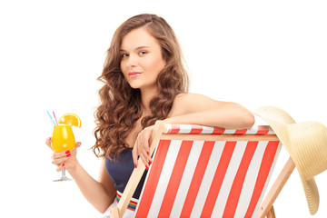 Young female sitting on a sun lounger and drinking a cocktail