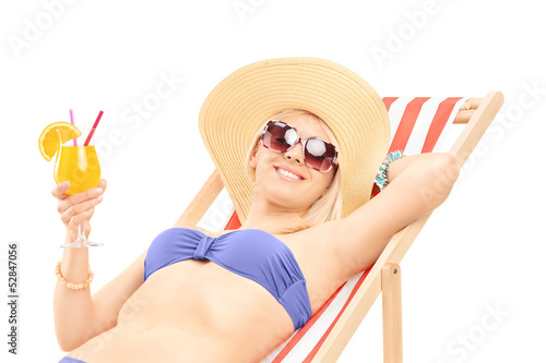 Smiling young woman sunbathing and holding a cocktail