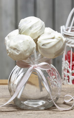 White chocolate cake pops in glass jar on wooden background