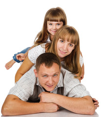 Happy family playing at home, lying heaped on floor. isolated