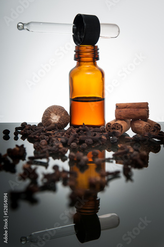 Various spices with essential oil bottle and dropper