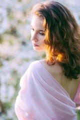 Young beautiful woman in blooming gardens