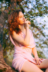 Young beautiful woman sitting on a tree in blooming gardens