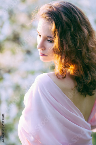 Young beautiful woman in blooming gardens