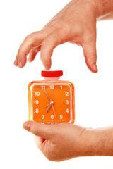 orange alarm clock in a hand on a white background.