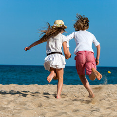Boy and girl running towards sea.
