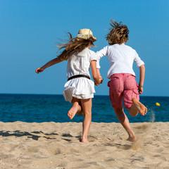 Boy and girl running towards sea.