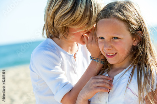 Boy whispering secrets to girl outdoors.