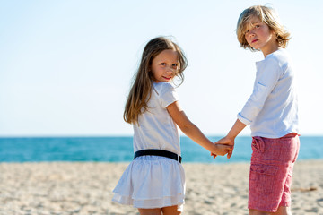 Two friends holding hands on beach.