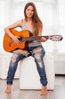 Young beautiful woman playing guitar