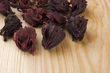 Dry hibiscus tea flowers on table