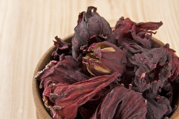 Dry hibiscus tea flowers in wooden bowl close up
