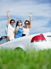 Group of girls stands in the cabriolet with hands up