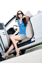 Pretty woman in sunglasses sits in the car