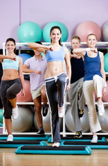 Group of people exercise at the gym on step boards