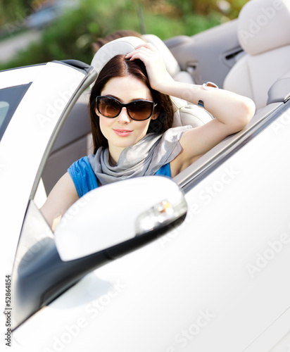 Portrait of dreamy woman wearing sunglasses in the car