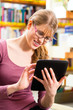 student in library learning with tablet computer