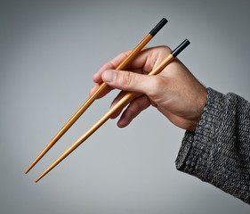 Male hand with chopsticks
