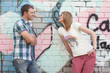 young couple against graffiti wall