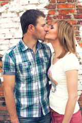 Couple kissing on brick wall background