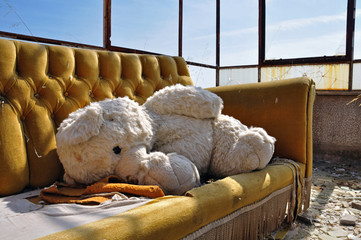 teddy bear and couch in abandoned building