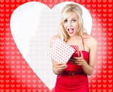 Surprised attractive girl with heart gift box