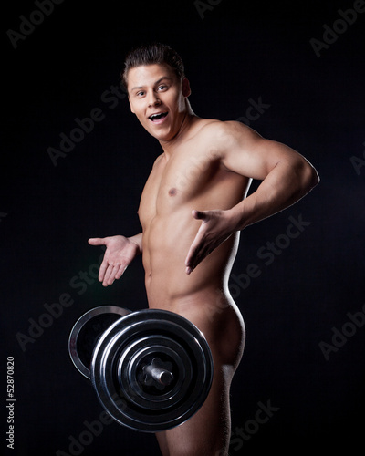 Portrait of astonished naked athlete with barbell