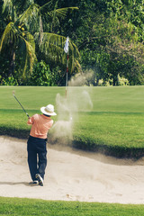Asian golfer in bunker on golf course