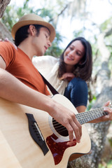 Young man playing guitar for woman in trees