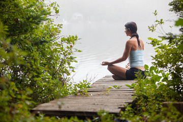Woman meditating on dock by lake